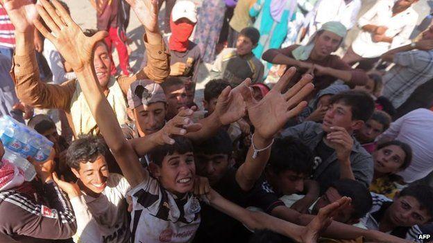 Displaced Iraqi Yazidis, who fled a jihadist onslaught on Sinjar, gather to collect bottles of water at the Bajid Kandala camp in Kurdistan's western Dohuk province, 13 August 2014