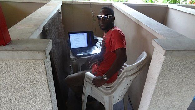 A person working on their laptop in an old cell of the prison in Lagos, Nigeria