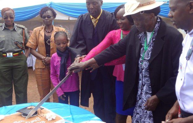 Peter Ouko, his daughter and mother cut a giant cake make for his graduation, Kamiti prison in Nairobi, Kenya - Friday 15 August 2014