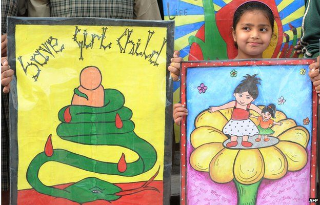 Indian schoolgirls pose with placards during a protest march against female foeticide in Amritsar on March 23, 2012.