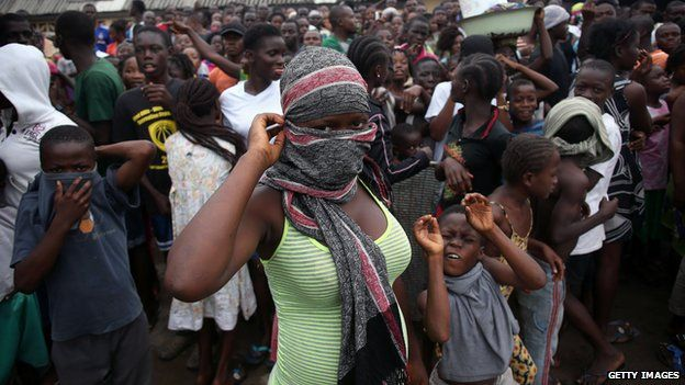 A crowd enters the grounds of an Ebola isolation center in the West Point slum on August 16