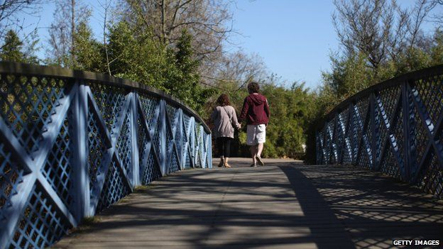 A couple holding hands on a bridge