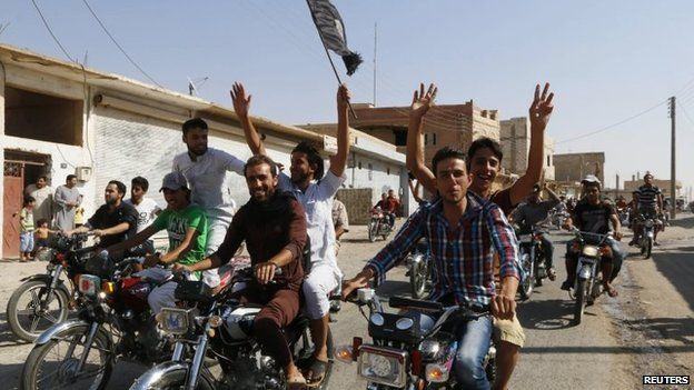 Residents of Tabqa city tour the streets on motorcycles, carrying flags in celebration after Tabqa air base fell