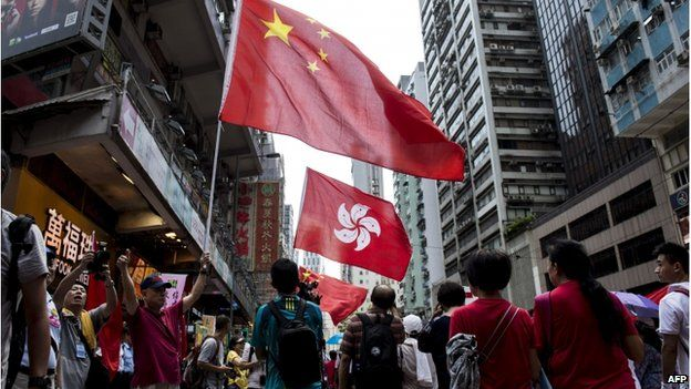 People hold the Chinese and Hong Kong flags as they take part in a pro-government rally in Hong Kong on 17 August 2014