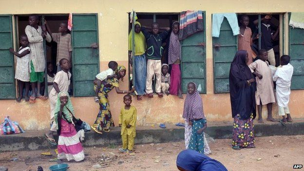 """A picture taken on August 21, 2014 shows Internally Displaced People (IDP) standing outside a classroom they found shelter in, at Gulak camp in Nigeria""""s northeastern Adamawa State."""