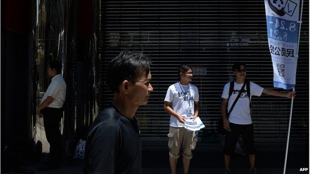 Volunteers display a banner and give out flyers on a street to raise awareness of an unofficial referendum in Macau on 24 August 2014.