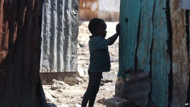 A child plays amidst tin shacks in the Cite Soleil district of Port-au-Prince, Haiti on Saturday, March 13, 2004.