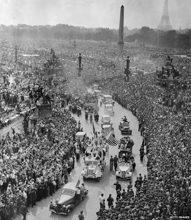 A large crowd gathers on August 26, 1944 to cheer French General Charles de Gaulle at Place de la Concorde during a military parade on the Champs Elysees