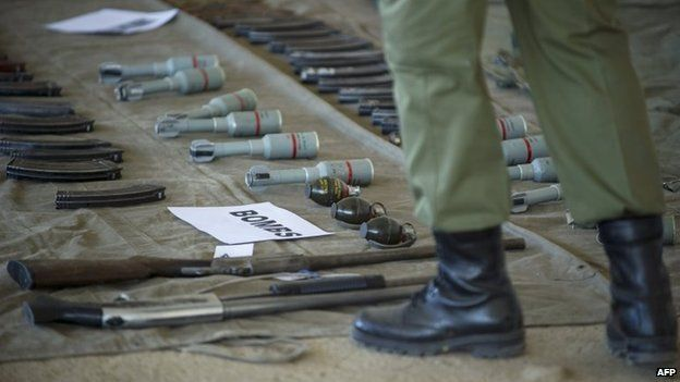 A soldiers stands near weapons displayed on September 1, 2014 at the Makoanyane Barracks in Maseru, during a press conference to present 130 firearms and a number of explosives confiscated from the police after military raided police installations.
