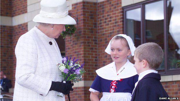 "A Dame Allan's girl meets the Queen wearing a ""Polly Bell"""