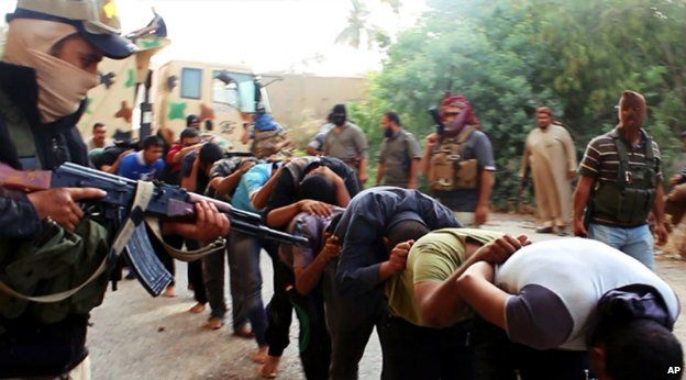 Islamic State fighters lead away captured Iraqi soldiers after taking over a base in Tikrit, Iraq - 14 June 2014