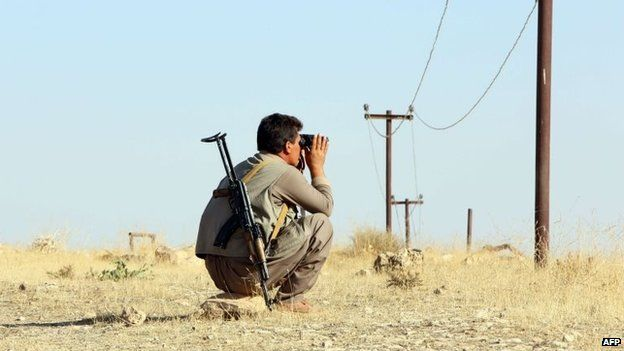 An Iraqi Peshmerga fighter scans the area as he holds a position at a post near the jihadist-held city of Zumar in Mosul province - 4 September 2014