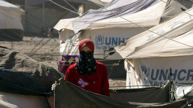 A woman looks out from her tent at an internally displaced persons camp in Irbil, Iraq on Thursday 4 September 2014