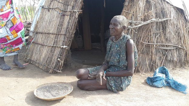 A woman sitting outside her make- shift home in Reke village, South Sudan, with a tray of water lily seeds in front of her
