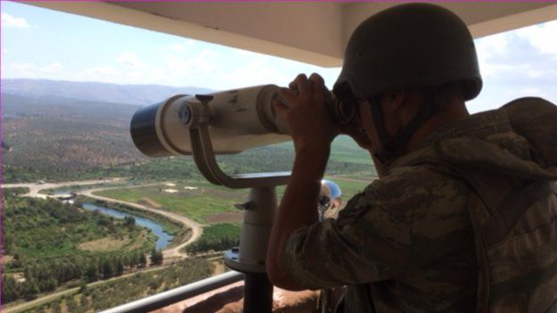 A Turkish serviceman monitors border