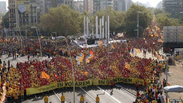 """People form a """"V"""" for """"vote"""" in red and yellow, the colours of the Catalan flag, during a gathering to mark the Calatalonia day """"Diada"""" in central Barcelona, 11 September 2014"""