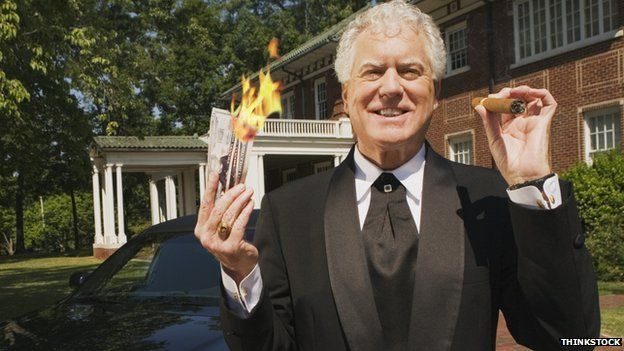 A wealthy man holds burning money.