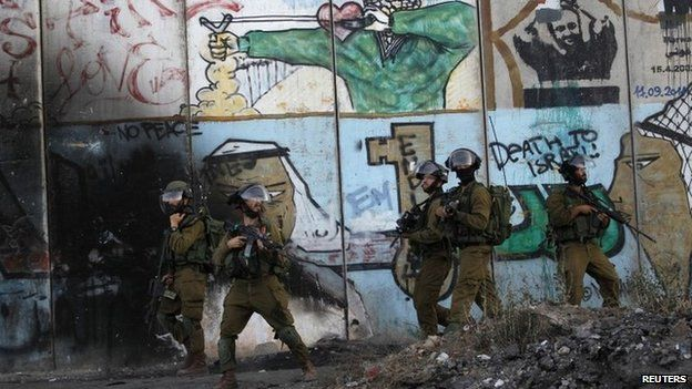 Israeli soldiers patrol near the Qalandia checkpoint in the West Bank (13 August 2014)