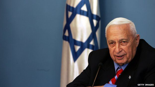 Former Israeli Prime Minister Ariel Sharon speaking into a mic at a press conference. The Israeli flag hands behind him