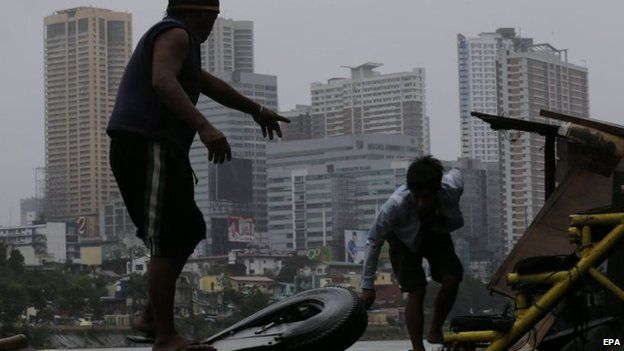Filipinos secure their property from rain along a swelling river in Makati, Manila