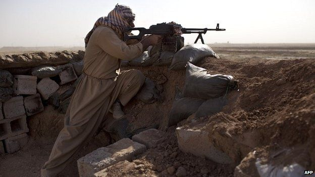 A Kurdish fighter fires towards Islamic States militants during clashes 50km east of Tikrit, Iraq - 11 September 2014
