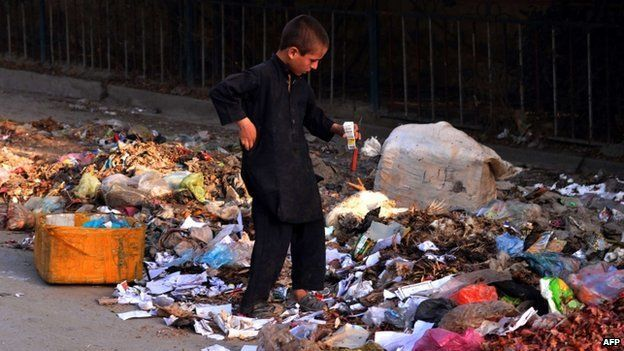 An Afghan child labourer collects cardboard and other materials from a rubbish heap on the outskirts of Jalalabad on August 8, 2014.