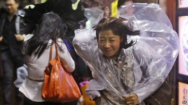 A woman braves strong wind in Hong Kong on 15 September 2014