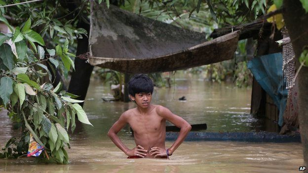 A Filipino boy wades through waist-deep floodwaters at a village located beside a swollen river as it slowly recedes in suburban Quezon city, Philippines on 15 September 2014