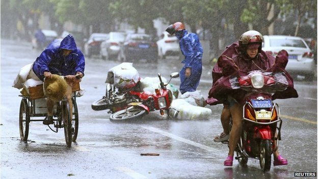 A motorcycle (centre) falls on the street as residents ride their vehicles against strong wind and heavy rainfall under the influence of Typhoon Kalmaegi, in Haikou, Hainan province 16 September 2014.