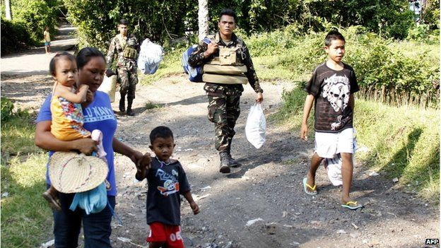 Philippine military personnel (back) help residents evacuate from their village in Camalig town, Albay province on 16 September 2014, as authorities imposed a forced evacuation of residents due to Mayon volcano's imminent eruption