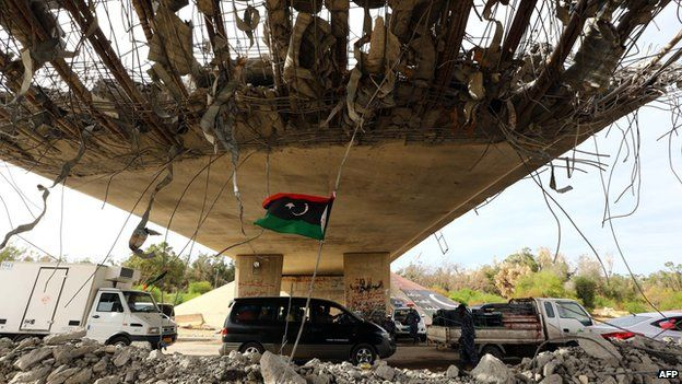 A Libyan flag flutters as cars wait under a bridge on 9 September 2014 at a police checkpoint erected on a main road near a former army camp where clashes took place between rival militias at the western entrance of the capital Tripoli