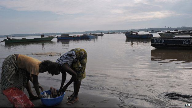 Women clean fish as they wait for fishermen on 21 January 2010 in the fishing port of Cabinda, Angola