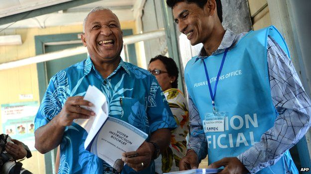 Fijian military strongman Voreqe Bainimarama (left) shares a light moment with an election official before casting his election vote at the Vatuwaqa Public School in the capital Suva on 17 September, 2014