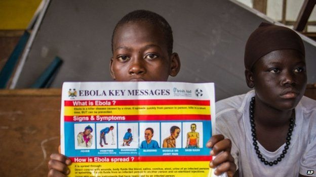 A child holds up a poster which details ways to identify the Ebola virus in Freetown, Sierra Leone (18 September 2014)