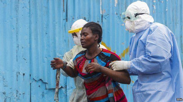 Liberian nurses escort a suspected Ebola patient into the John F. Kennedy (JFK) Ebola treatment centre in Monrovia (18 September 2014)