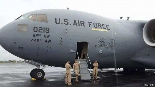 American air force soldiers stand outside a US military aircraft after landing at Roberts International Airport outside Monrovia (19 September 2014)