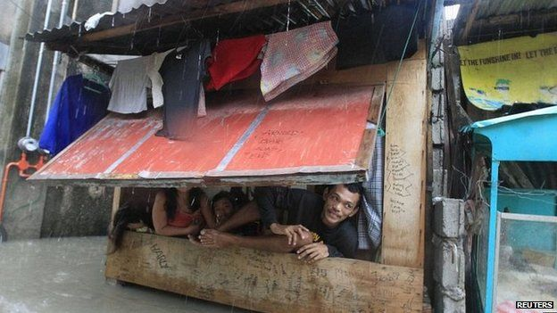 Manila residents shelter in a shanty dwelling amid floodwater (19 Sept 2014)