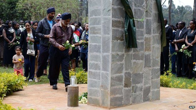 Relatives of victims of the Westgate attack carry flowers during a memorial service at the Amani Garden in Nairobi, Kenya - September 21, 2014
