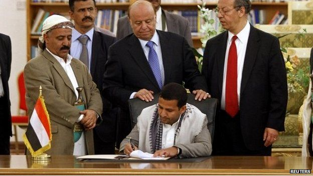 Hussein al-Ezzi, the Houthi's head of political relations, signs the agreement at a ceremony in Sanaa - 21 September 2014