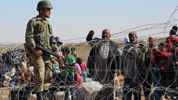 Turkish soldier stands guard as Syrian refugees wait to cross border in Suruc, Turkey. 21 Sept 2014