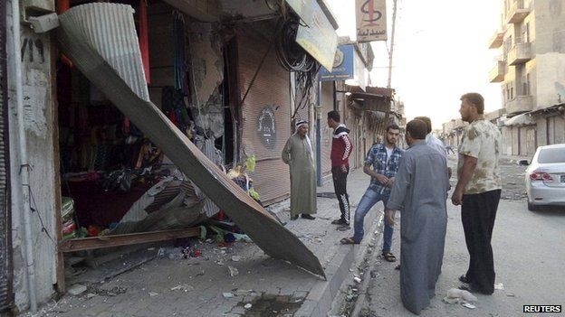 People inspect a shop damaged after what Islamist State militants say was a US drone crash in Raqqa - 23 September 2014