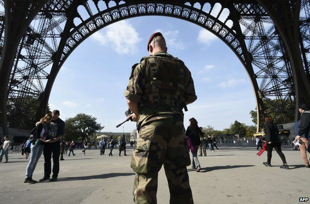 A French paratrooper patrols near the Eiffel Tower in Paris, 23 September
