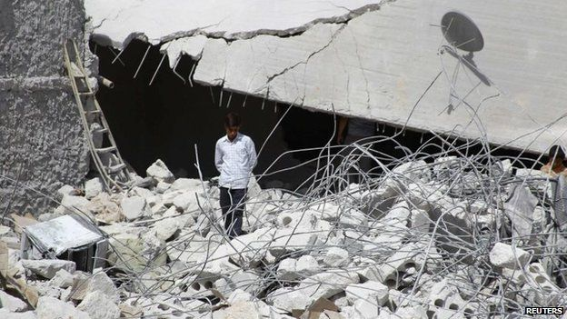 A resident walks upon the debris of buildings which were damaged in what activists say was one of Tuesday's US air strikes in Kfredrian, Idlib province, 24 September 2014