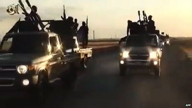 An image grab taken from a video released by Islamic State group's official Al-Raqqa site via YouTube on 23 September 2014, allegedly shows Islamic State (IS) group recruits riding in armed trucks in an unknown location