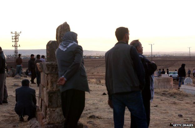 Turkish residents at Suric look across the border into Syria as fighting continues, 28 September