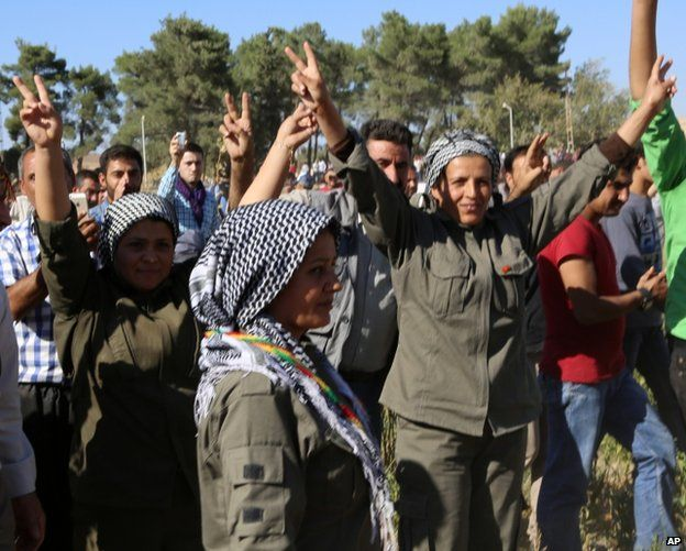 Syrian Kurdish female fighters from Kobane celebrate after other Kurds from Turkey and Syria break down wire on the Turkish border, 26 September