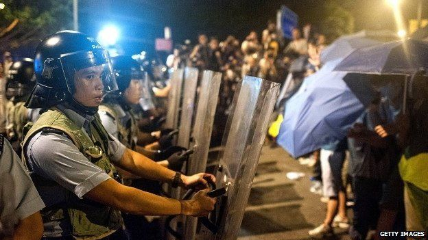 Police officers trying to defend Hong Kong's government complex from protesters on 27 September 2014