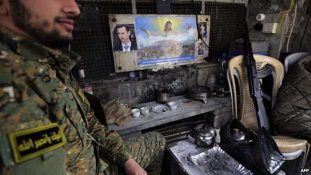 A member of the Syrian National Defence Forces (NDF) sits at his post at the entrance to the Old City of Damascus (January 2014)