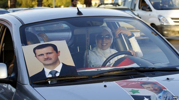 Supporter of Syrian President Bashar al-Assad drives a car covered in posters of him in Damascus (11 September 2013)