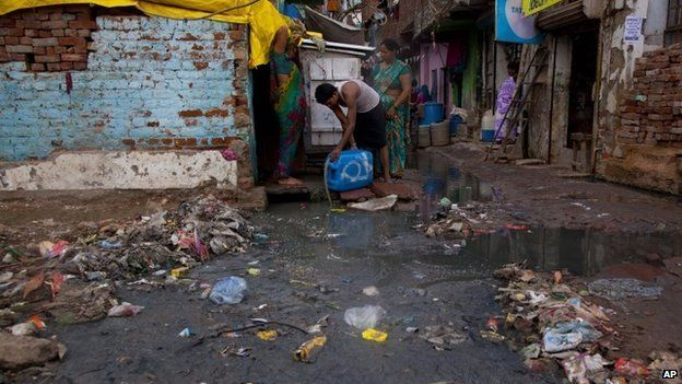 In this Thursday, Aug. 28, 2014 photo, a man fills drinking water from a tap covered by stagnant water and garbage in New Delhi, India